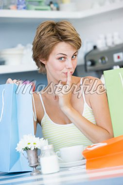 A young woman sitting in a cafe with shoping bags Stock Photo - Royalty-Free, Artist: MonkeyBusinessImages, Code: 400-04037722