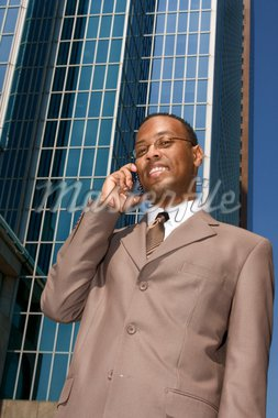 Businessman on the phone outdoors on background of reflective office building Stock Photo - Royalty-Free, Artist: mocker, Code: 400-04039262