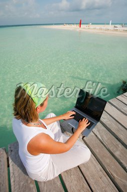 Woman using her laptop on a jetty next to a tropical beach Stock Photo - Royalty-Free, Artist: Spanishalex, Code: 400-04064547