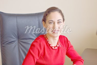 Smiling, attractive brunette businesswoman at her desk, dressed in bright red, isolated against white. Stock Photo - Royalty-Free, Artist: DTPhoto, Code: 400-04072344