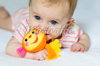 Baby girl lying on her tummy on a white blanket playing with colourful monkey Stock Photo - Royalty-Free, Artist: myadria, Code: 400-04081145