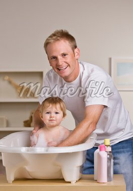 A young father is giving his baby daughter a bath in a childs bathtub.  He is smiling at the camera.  Vertically framed shot. Stock Photo - Royalty-Free, Artist: avava, Code: 400-04124026