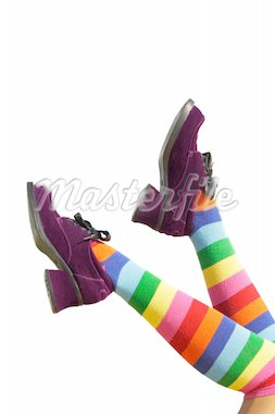 Striped knee-hi socks and wickedly wonky, purple suede shoes on isolated girl's legs.  Stock Photo - Royalty-Free, Artist: songbird, Code: 400-04155884