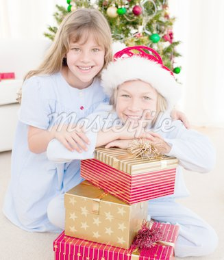 Smiling siblings holding Christmas gifts and sitting on the floor Stock Photo - Royalty-Free, Artist: 4774344sean, Code: 400-04156820