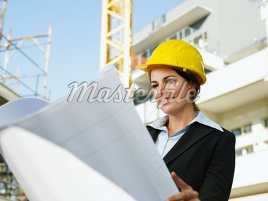 female engineer looking at blueprints in construction site Stock Photo - Royalty-Free, Artist: diego_cervo, Code: 400-04158093
