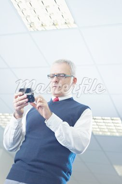 portrait of mature business man typing on mobile phone. Low angle view, Copy space Stock Photo - Royalty-Free, Artist: diego_cervo, Code: 400-04163910