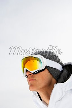 Head shot of a male skier wearing ski goggles against a snowy white background. Vertical shot. Stock Photo - Royalty-Free, Artist: iofoto, Code: 400-04169435