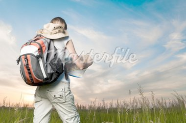 beautiful young woman with backpack and map in hand standing outside in the field with her back to camera. Sunset cloudy blue sky in background and green grass in foreground Stock Photo - Royalty-Free, Artist: kyolshin, Code: 400-04200702