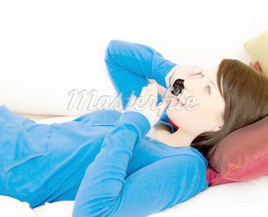 Surprised female teenager talking on phone lying on a sofa in the living room Stock Photo - Royalty-Free, Artist: 4774344sean, Code: 400-04206736