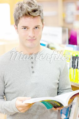 Serious young man reading a book in a bookstore Stock Photo - Royalty-Free, Artist: 4774344sean, Code: 400-04224787