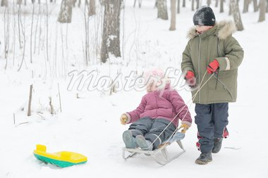 Winter games children - a girl on a sledge and a boy next. Stock Photo - Royalty-Free, Artist: vblinov                       , Code: 400-04262017