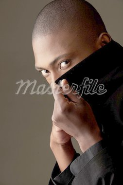 Young professional black african adult businessman in a black suit with a pink tie and dark coat on a dark grey background. Not Isolated Stock Photo - Royalty-Free, Artist: Forgiss                       , Code: 400-04277911