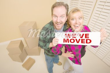 Goofy Couple Holding We've Moved Sign in Room with Packed Cardboard Boxes. Stock Photo - Royalty-Free, Artist: Feverpitched                  , Code: 400-04298119
