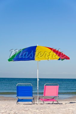 Pink and blue deck chairs on a beach underneath a colourful umbrella or parasol Stock Photo - Royalty-Free, Artist: darrenbaker                   , Code: 400-04316565