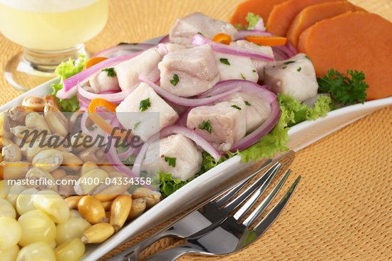 Peruvian-style ceviche made out of raw dogfish (Spanish: tollo), red onions and aji (Peruvian hot pepper) and served with corn, roasted corn (cancha) and sweet potato with Pisco Sour (Peruvian traditional cocktail) in the back (Selective Focus, Focus on the front of the fish) Stock Photo - Royalty-Free, Artist: ildi                          , Code: 400-04334358