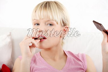 Young beautiful woman eating chocolate. Stock Photo - Royalty-Free, Artist: BDS                           , Code: 400-04351599