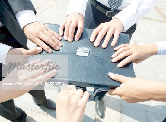 Close-up of people hands holding black leather briefcase simultaneously Stock Photo - Royalty-Free, Artist: pressmaster                   , Code: 400-04356730