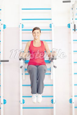 A young girl making exercises on exercise machine Stock Photo - Royalty-Free, Artist: pressmaster                   , Code: 400-04359439