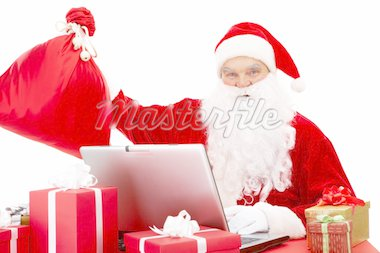 Portrait of Santa Claus in front of laptop with gifts near by Stock Photo - Royalty-Free, Artist: pressmaster                   , Code: 400-04362961