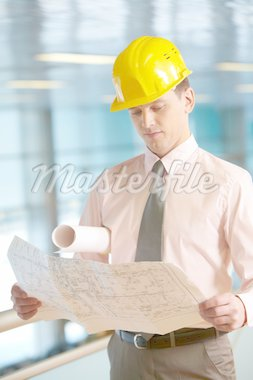 Young architect in helmet examining a housing plan Stock Photo - Royalty-Free, Artist: pressmaster                   , Code: 400-04363871