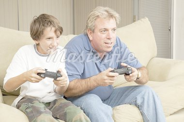 Father and son or uncle and nephew, playing video games at home. Stock Photo - Royalty-Free, Artist: lisafx                        , Code: 400-04374238