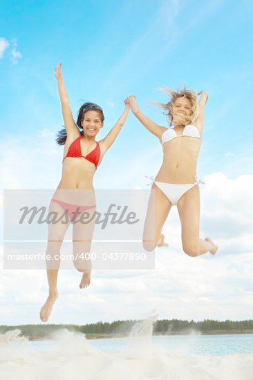 Portrait of young girls in bikini jumping during summer vacation Stock Photo - Royalty-Free, Artist: pressmaster                   , Code: 400-04377890
