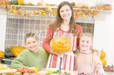 Mother and two children carving jack o lanterns on Halloween and Stock Photo - Royalty-Free, Artist: MonkeyBusinessImages          , Code: 400-04402193
