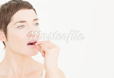 Close up of a woman taking a pill against a white background Stock Photo - Royalty-Free, Artist: 4774344sean                   , Code: 400-04410435