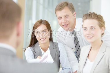 Two happy managers looking at business partner at meeting Stock Photo - Royalty-Free, Artist: pressmaster                   , Code: 400-04416228