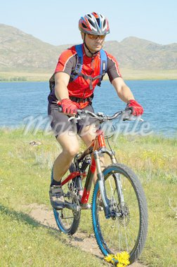 Bike tourist on green field beside lake Stock Photo - Royalty-Free, Artist: Petrichuk                     , Code: 400-04527059