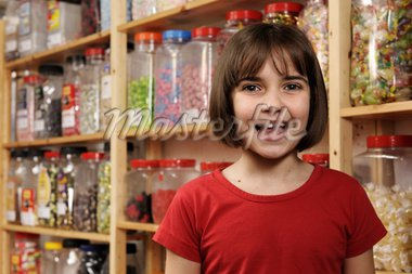 young girl smiling at camera in sweet shop Stock Photo - Royalty-Free, Artist: gemphotography                , Code: 400-04589354