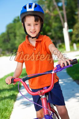 A young boy child cycling on his bicycle and wearing a helmet Stock Photo - Royalty-Free, Artist: darrenbaker                   , Code: 400-04728104