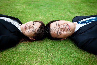 Attractive young adult couple and lay on the grass field Stock Photo - Royalty-Free, Artist: tomwang                       , Code: 400-04839921