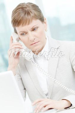 Photo of smart businesswoman calling while typing on laptop keypad Stock Photo - Royalty-Free, Artist: pressmaster                   , Code: 400-04878472