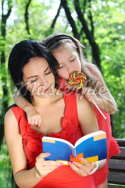 Little girl and mother reading the book in the garden. Stock Photo - Royalty-Free, Artist: sriba3                        , Code: 400-04902586