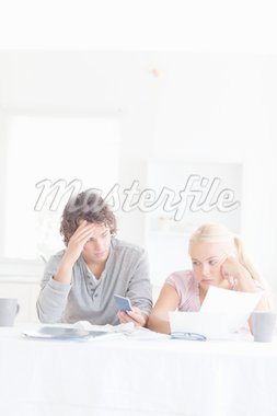 Despaired couple calculating in their living room Stock Photo - Royalty-Free, Artist: 4774344sean                   , Code: 400-04904930