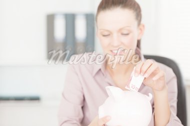 A woman putting money into piggy bank Stock Photo - Royalty-Free, Artist: 4774344sean                   , Code: 400-04905252