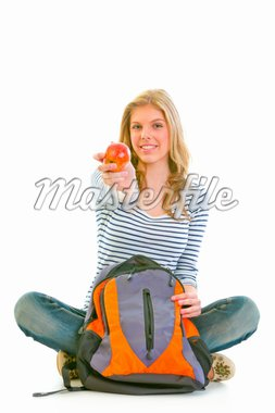 Cheerful teenager sitting on floor with schoolbag and giving apple isolated on white    Stock Photo - Royalty-Free, Artist: citalliance                   , Code: 400-04909952