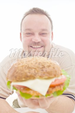 Man happy with the size of his hamburger holding it happily - closeup, isolated Stock Photo - Royalty-Free, Artist: lightkeeper                   , Code: 400-04916215