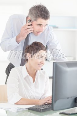 Man making a phone while looking at his colleague's screen in an office Stock Photo - Royalty-Free, Artist: 4774344sean                   , Code: 400-04918073