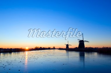 The sun rises over rural holland in wintertime, with windmills and an ice covered, frozen, canal Stock Photo - Royalty-Free, Artist: corepics                      , Code: 400-04923878