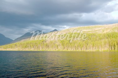 Sunlight illuminates the shoreline of Kintla Lake against a stormy sky in Glacier National Park - USA. Stock Photo - Royalty-Free, Artist: Wirepec                       , Code: 400-04924987