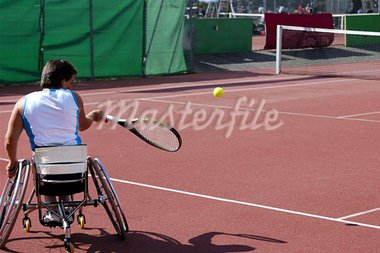 A wheelchair tennis player during a tennis championship match, taking a shot. Stock Photo - Royalty-Free, Artist: Bateleur                      , Code: 400-04975736