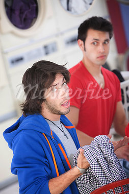 Unhappy Latino man holds clothes in laundromat Stock Photo - Royalty-Free, Artist: creatista                     , Code: 400-05347606