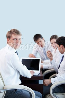 Young businessman with laptop on the background of employees in the office Stock Photo - Royalty-Free, Artist: Deklofenak                    , Code: 400-05348857