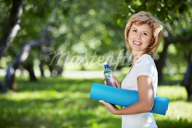Mature woman in a park with a bottle and gym mat Stock Photo - Royalty-Free, Artist: Deklofenak                    , Code: 400-05348863