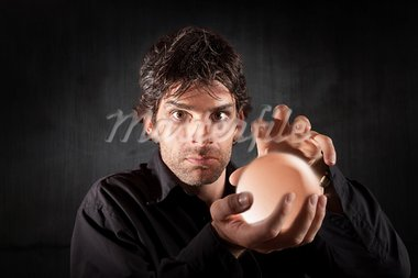 Serious fortune teller holds crystal ball over maroon background Stock Photo - Royalty-Free, Artist: creatista                     , Code: 400-05353790