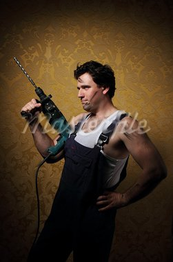 The builder holds the professional puncher-hammer with a drill Stock Photo - Royalty-Free, Artist: DashaPetrenko                 , Code: 400-05374349