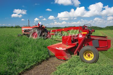 A mower drawn beside a tractor cuts a field of alfalfa in southern Wisconsin. Stock Photo - Royalty-Free, Artist: wakr10                        , Code: 400-05379120