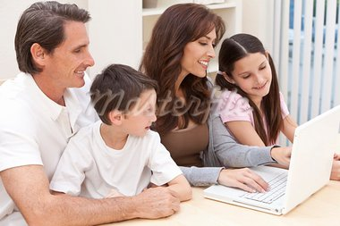 An attractive happy, family of mother, father, son and daughter sitting at table at home having fun using a laptop computer Stock Photo - Royalty-Free, Artist: darrenbaker                   , Code: 400-05385971